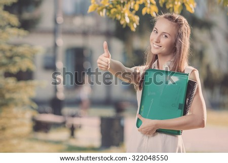 Happy smiling student woman is standing in the university campus and showing thumb up for a successfull year in college.  - stock photo