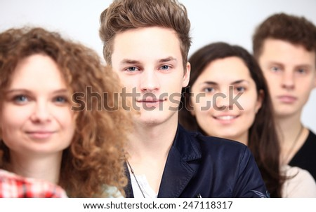 Happy Smiling Students Standing In Row. Young people standing in a row while beautiful young man standing in front of them and smiling