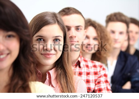 Happy Smiling Students Standing In Row. Young people standing in a row while beautiful young woman standing in front of them and smiling