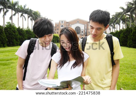 Happy smiling students standing together with books at a campus - stock photo
