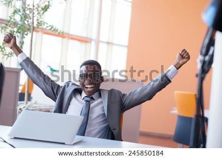 Happy smiling successful African American businessman  in a suit in a modern bright office indoors - stock photo