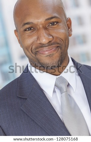 Happy smiling successful African American businessman or man in a suit in a modern city