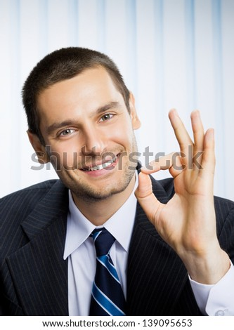 Happy smiling successful gesturing business man with okay hand sign at office