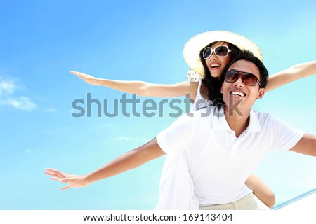Happy smiling summer couple piggyback together with arms outstretched at beautiful beach - stock photo