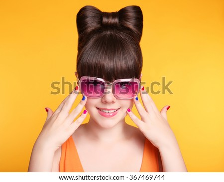 Happy smiling teen girl with fashion sunglasses, bow hairstyle and colourful manicured polish nails. Funny girl showing ten fingers isolated on studio yellow background. - stock photo