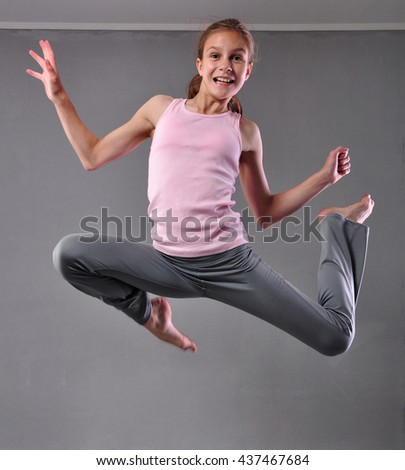Happy smiling teenage girl dancer skipping jumping and dancing on grey background. Child exercising. Sport healthy lifestyle concept. Sporty childhood. - stock photo