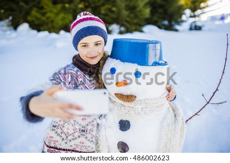 Happy smiling teenage girl taking selfie with a snowman on a snowy winter village in mountains, Switzerland