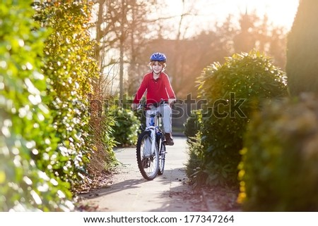 Happy smiling teenager boy riding his bike on sunset - stock photo