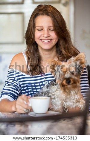 Happy smiling teenager  girl holding little dog at coffee - stock photo