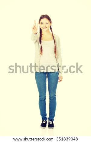 Happy smiling teenager showing victory gesture. - stock photo