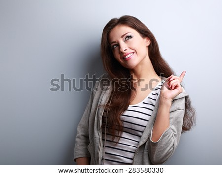Happy smiling thinking woman have an idea and looking up on blue background - stock photo