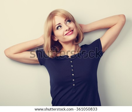 Happy smiling thinking young casual woman relaxing and looking up. Toned closeup portrait