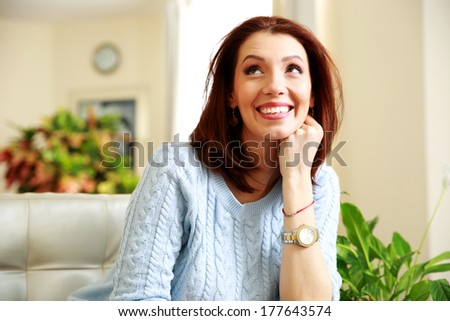 Happy smiling thoughtful woman looking up at home - stock photo