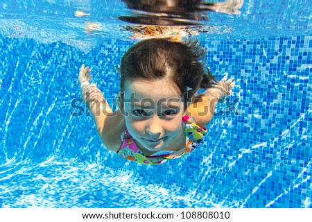 Happy smiling underwater child in swimming pool, beautiful girl swims and having fun. Kids sport on family summer vacation. Active holiday - stock photo