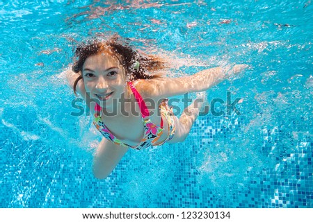 Happy smiling underwater child in swimming pool, beautiful healthy girl swims and having fun in water. Kids sport on family summer vacation. Active holiday