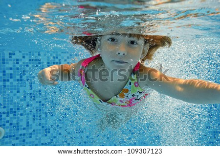 Happy smiling underwater child jumps to swimming pool, beautiful little girl swims and having fun. Kids sport on family summer vacation. Active holiday
