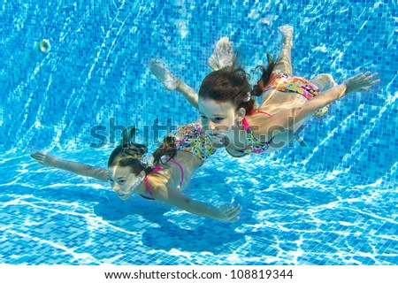 Happy smiling underwater children in swimming pool, beautiful girls swim and having fun. Kids sport on family summer vacation. Active holiday - stock photo
