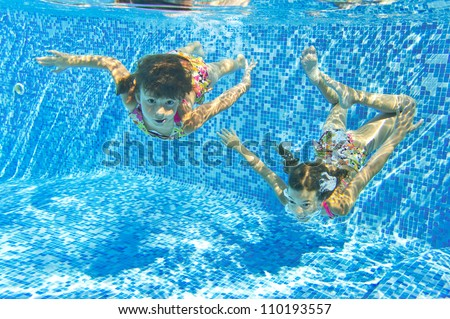Happy smiling underwater children in swimming pool, beautiful healthy girls swim and having fun in water. Kids sport on family summer vacation. Active holiday