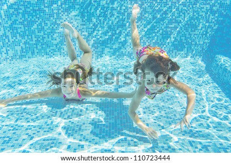 Happy smiling underwater children in swimming pool, beautiful healthy girls swim and having fun in water. Kids sport on family summer vacation. Active holiday - stock photo