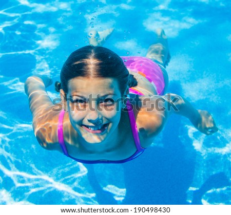 Happy smiling underwater girl in swimming pool. Active holiday - stock photo