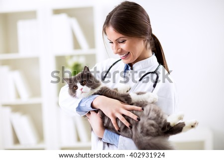 Happy smiling vet with patient at work - stock photo
