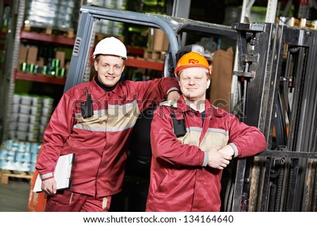 happy smiling warehouse workers in uniform in front of forklift stacker loader - stock photo