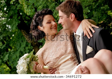 Happy smiling wedding couple outdoors. Man is holding woman with bunch of flowers in his arms. Find other nice peoples photos in my portfolio. - stock photo