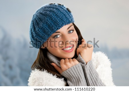 Happy smiling winter girl looking at camera outdoor in the snow