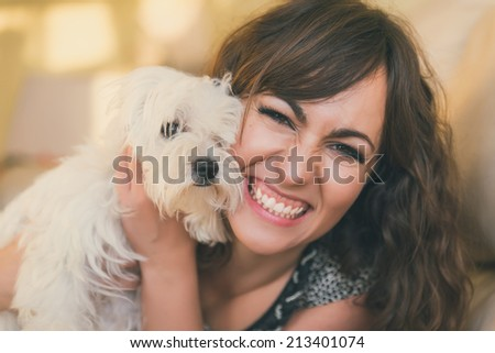 Happy smiling woman cuddling her small white curly haired pet dog close to her cheek with a beaming smile, close up portrait - stock photo