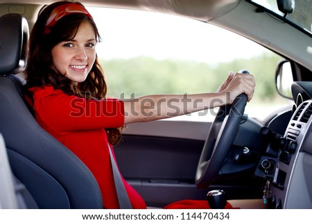 Happy smiling woman driving car, looking at camera - stock photo