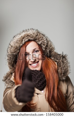 Happy smiling woman enjoying winter and giving thumbs-up while wearing a heavy winter coat with fur and gloves - stock photo