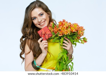 Happy smiling woman holding presents. Flowers and gift box. White background isolated.