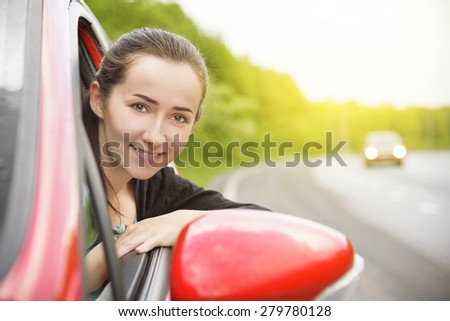 Happy smiling woman in a red car. At sunset. Travel concept. - stock photo