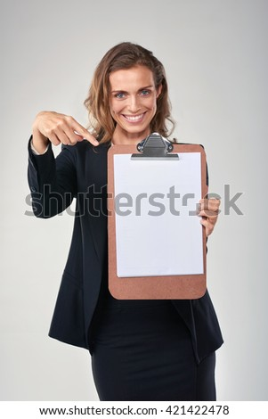 Happy smiling woman in business suit pointing to blank clipboard with copy space - stock photo