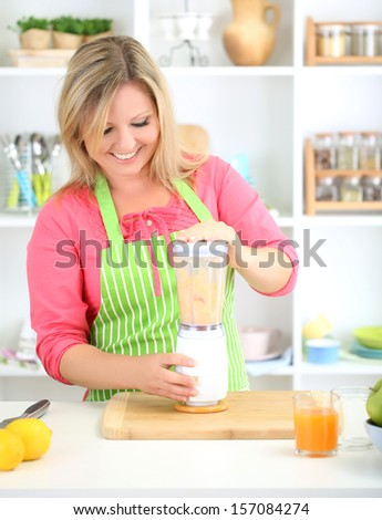 Happy smiling woman in kitchen preparing fresh fruit cocktail
