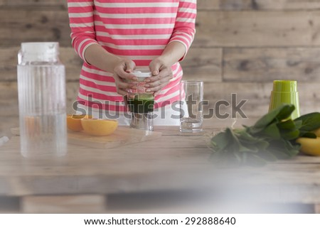 Happy smiling woman in kitchen preparing fresh fruit cocktail - stock photo