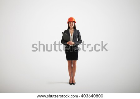 Happy smiling woman in lovely formal wear and construction helmet holding black folder in her hands