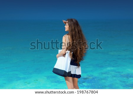 Happy smiling woman looking into a sea lagoon. Girl with Long hair over Blue sky. Summer beach vacation holidays.  - stock photo