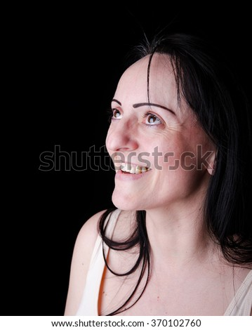 Happy smiling woman looking up towards a light source such as a screen. Black background with copy space. - stock photo