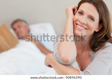 Happy smiling woman on the bed with husband reading behind her - stock photo