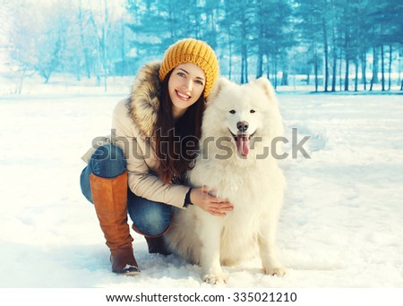 Happy smiling woman owner embracing white Samoyed dog in winter day - stock photo