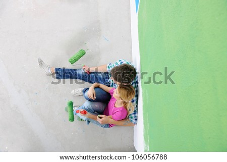 happy smiling woman painting interior white  wall in blue and green color of new house - stock photo