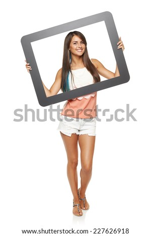 Happy smiling woman standing in full length looking through frame, over white background - stock photo