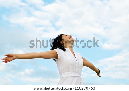Happy smiling woman standing with outspread arms and her face lifted to the cloudy blue sky - stock photo