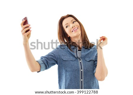 Happy smiling woman taking selfie with her mobile phone, isolated over white background - stock photo