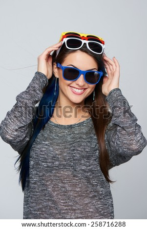 Happy smiling woman wearing many colourful sunglasses