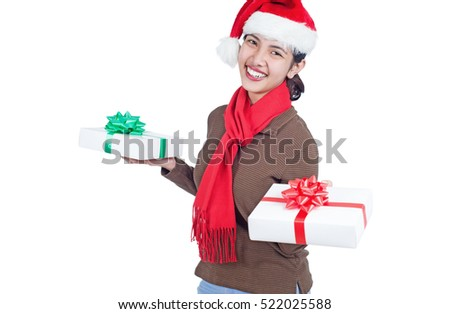 Happy smiling woman wearing Santa hat and holding gift boxes. Isolated in white background.