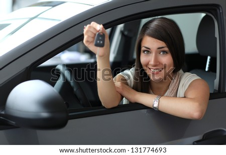 Happy smiling woman with car key. Driving