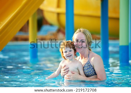 Happy smiling woman with child girl playing in waterpark  - stock photo