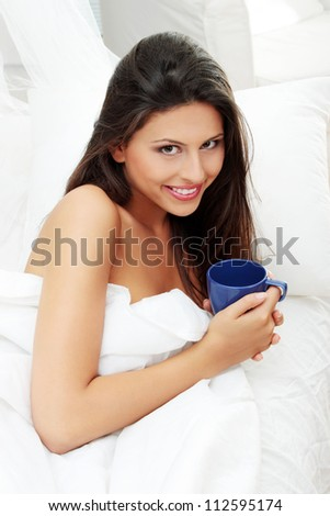 Happy smiling woman with cup of something hot in bed - stock photo